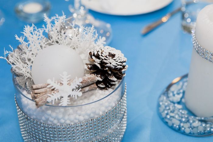 deco table de jour de l an avec des petits details de flocons de fausse neige et cones de pin sur une nappe bleue