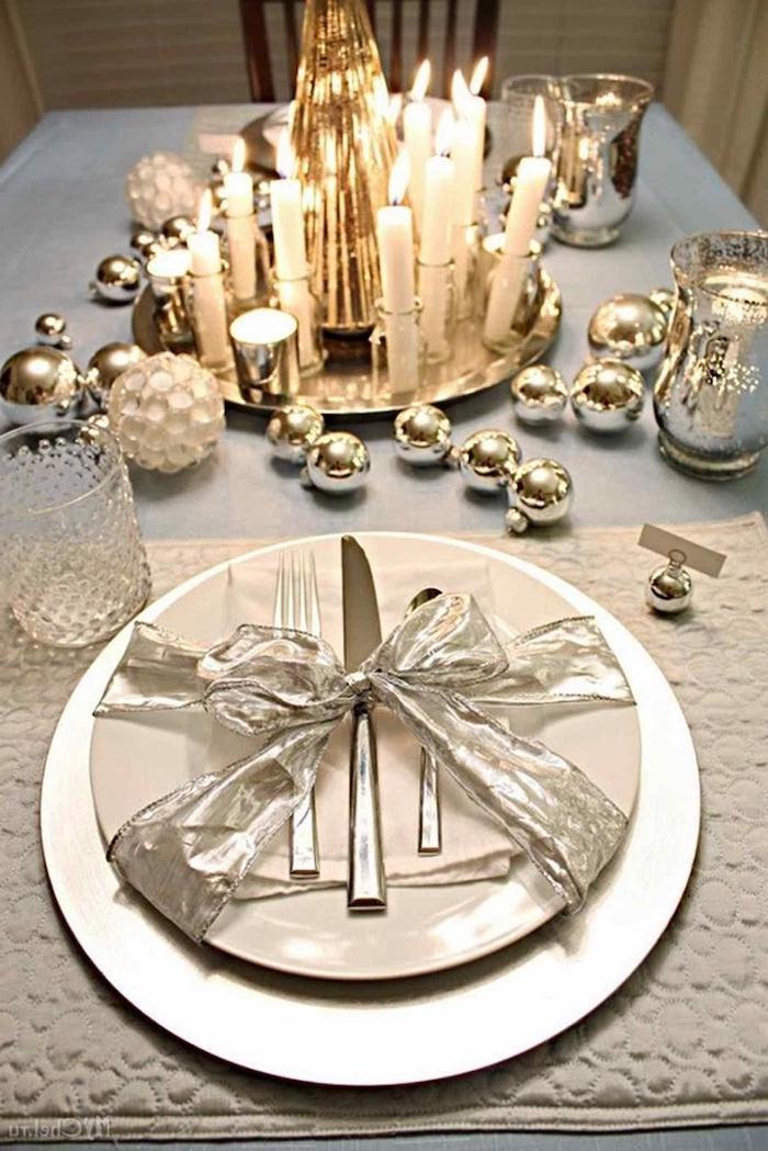 deco table jour de l an avec des couverts ergentines des boules de noel et un plateau scintillant avec des bougie