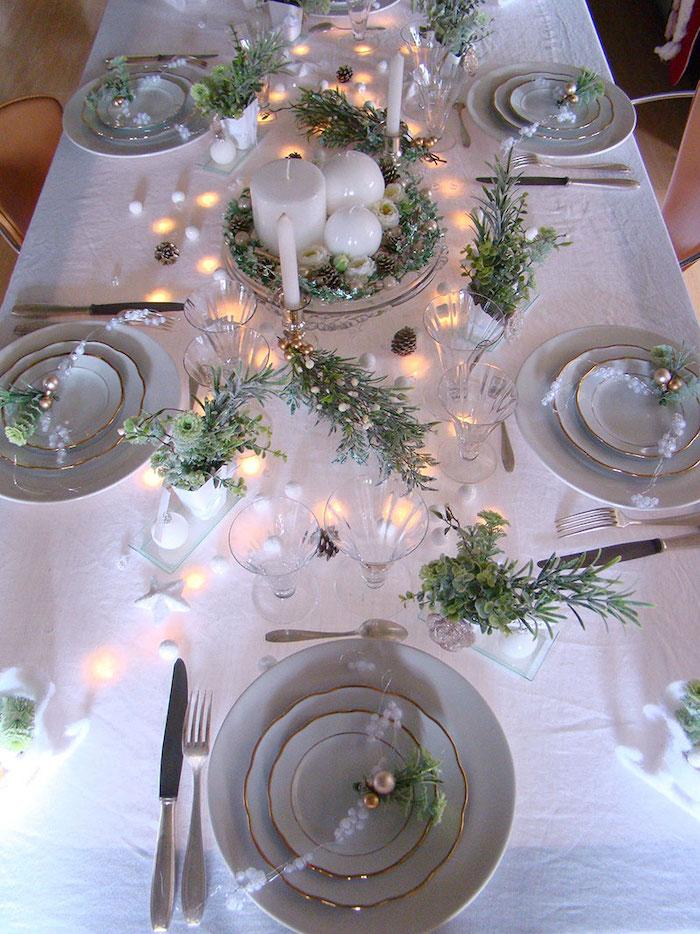 deco table jour de l an avec des elements verts et naturels des lampes de noel et des asiettes aux bordures dores