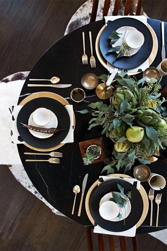 deco table nouvel an 2021 avec des couverts en or et un bouquet vert d artichaut decoration de plumes