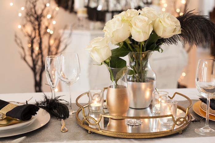deco table nouvel an avec des elements en or rose serviette noir et un bouquet de roses blanches