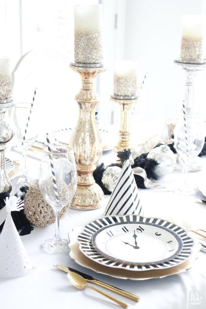 deco table nouvel an avec une assiette en dessin horloge un chandelier doree et guirlande noir