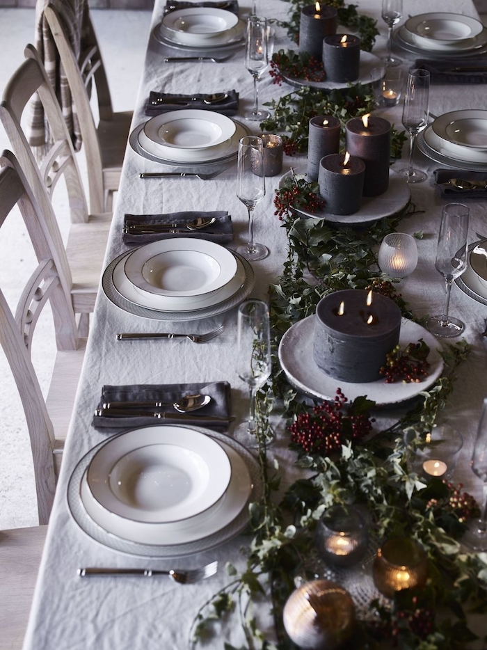 deco table reveillon saint avec une nappe blanche et decorations vertes baies des grandes bougies dans des assiettes