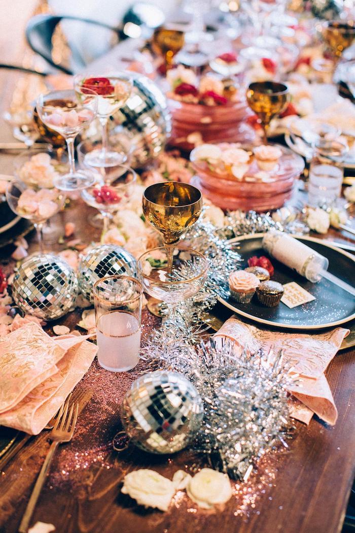 deco table reveillon st sylvestre avec des elements brillants et des balles disco des couverts et des verres dorres sur une table en bois