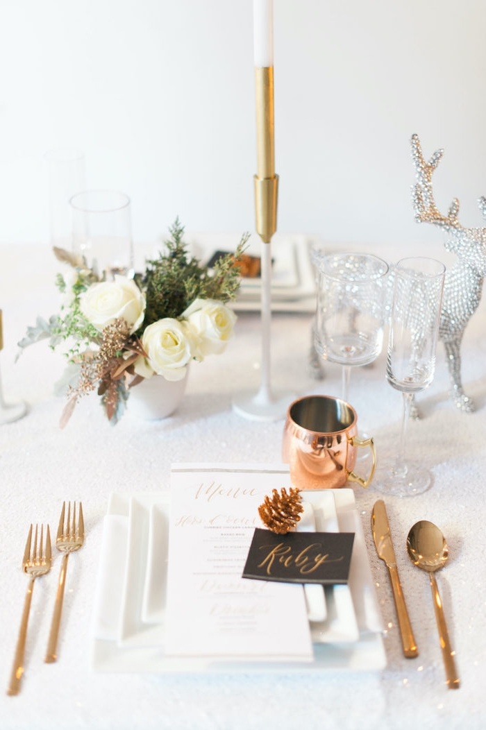 decoration de la table du nouvel an avec des fleurs blanches et des elementen cuivre un cerf en cristaux decratif