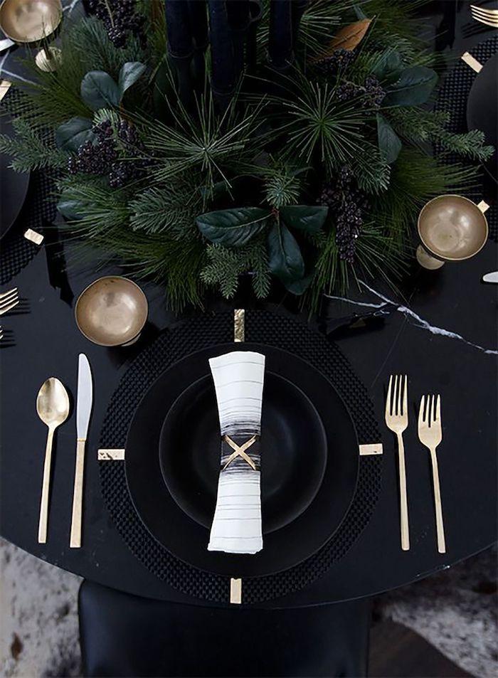 decoration de nouvel an sur une table noire avec des assiettes noires et couverts dores