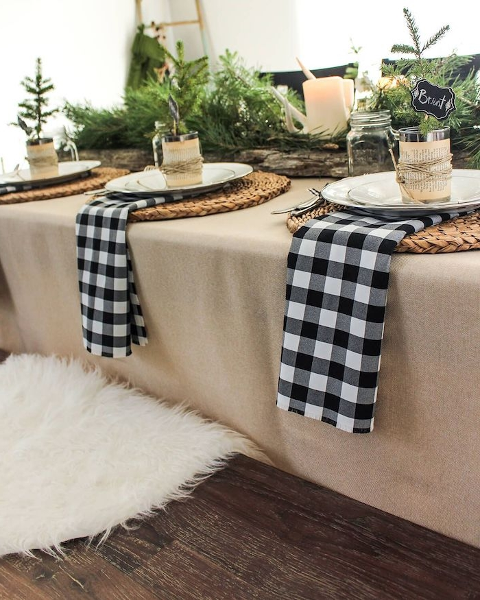 decoration de table pour noël avec des serviettes imprimées en carreaux noir et blanc des branches de sapin et des napperons en paille