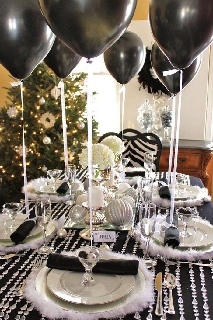 decoration nouvel an en noir et blanc avec des ballons et une nappe decore avec des guirlandes en cristaux
