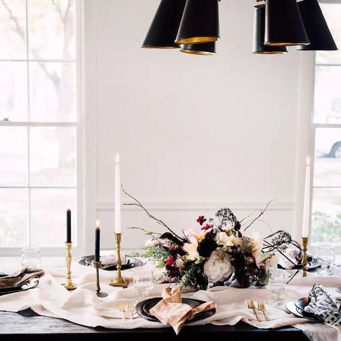 decoration reveillon nouvel an a faire avec des fleurs seches et des bougies noirs et blancs avec des couverts dores
