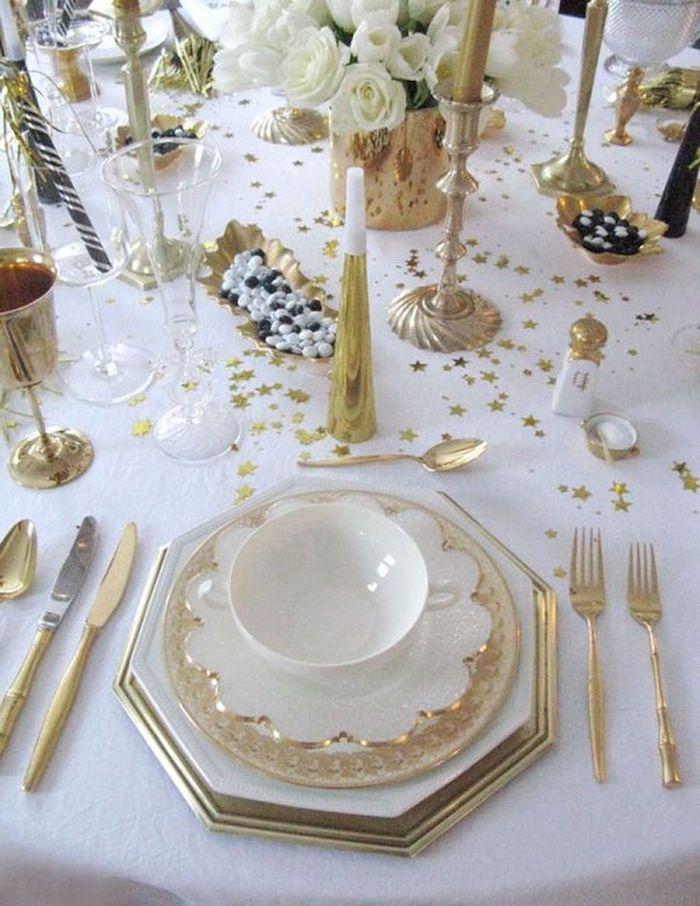 decoration table reveillon saint avec des asiettes blanches aux bordures dores des confettis parsemes sur une nappe blanche