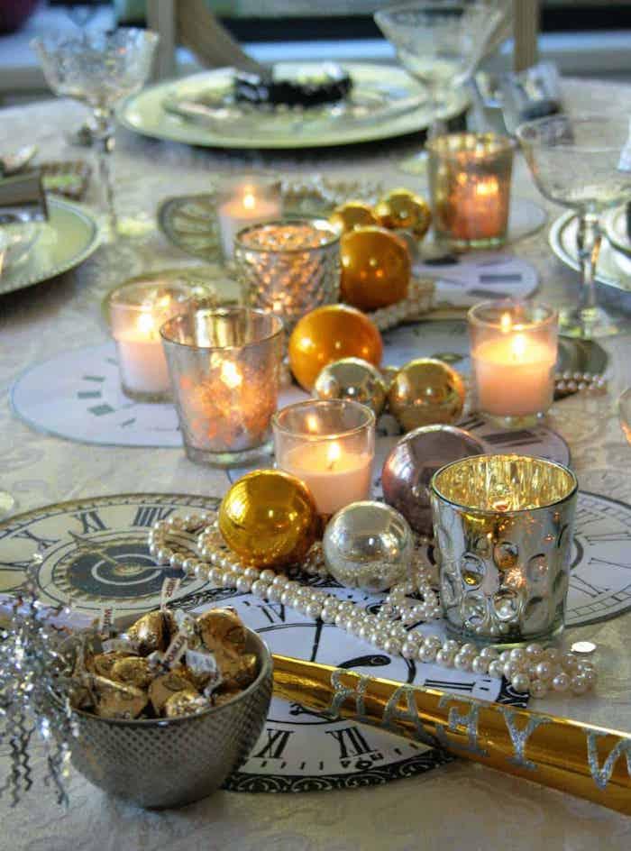 decoration table reveillon saint avec des bougies et bouels de noel un bol plaine de bonbons des napperons dessines commes des horloges
