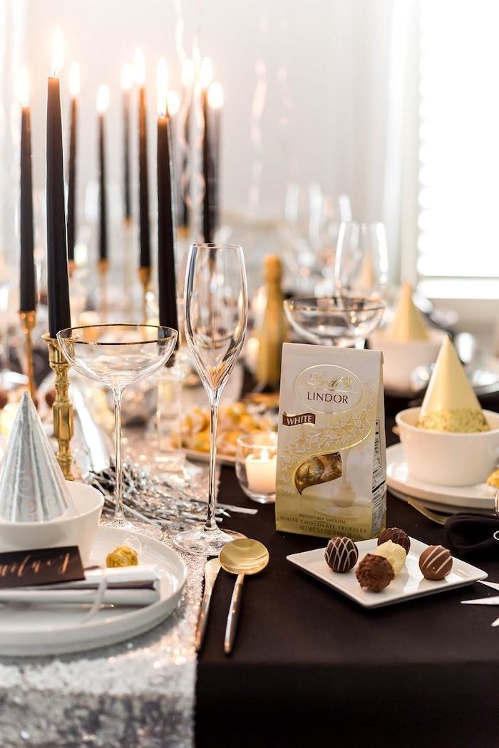 decoration table reveillon saint sylvestre des bougies longues noires un chemin de table argentine et une boite de bonbons de chocolat