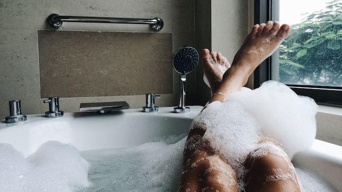 des jambes feminines dans une bain avec un plante verte visible par la fentre