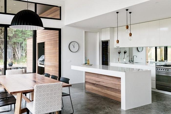 design intérieur agencement cuisine équipée moderne ouverte avec îlot blanc et bois lampe suspendue noire