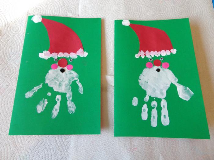 dessin père noel en empreinte de main sur papier vert avec chapeau papier rouge des yeux mobiles nez et joues papier