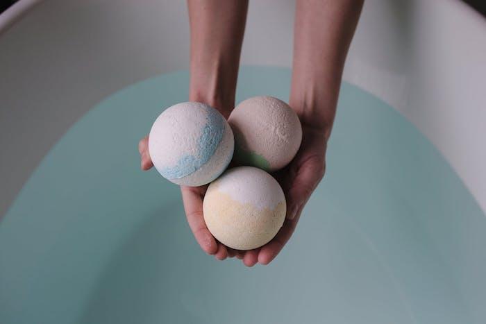 deux mains qui tiennent trois boules de bain fait maison au dessus d un bain plein d eau