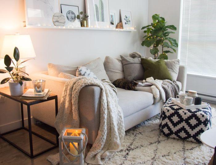etagere blanche ouverte surchargée d art canapé gris clair tabouret noir et blanc plante verte deco guirlande lumineuse plaid sur canapé gris lanterned ecorative