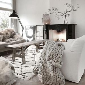 exemple de salon scandinave naturel avec table basse bois brut plaid grosses mailles sur canapé blanc tapis blanc fausse cheminée décorative noire