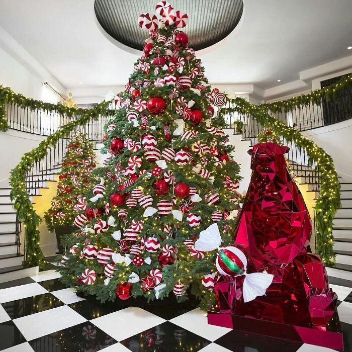 exemple de sapin rouge et blanc avec decoration de grandes boules de noel et des bonbons menthe pivrée sapin naturel et decoration d escalier nature