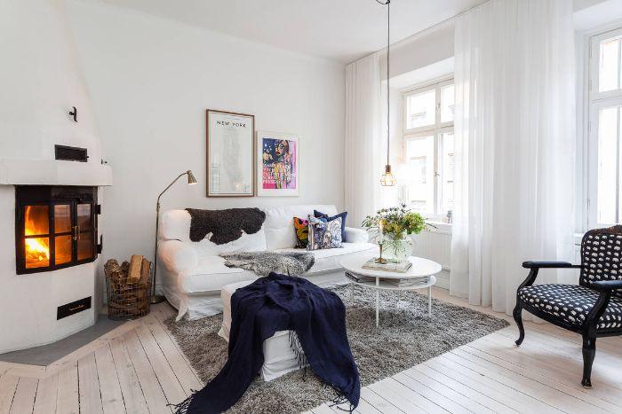 grande cheminée design blanche canapé blanc tapis gris cocooning couverture bleu marine table basse blanche rideaux blancs