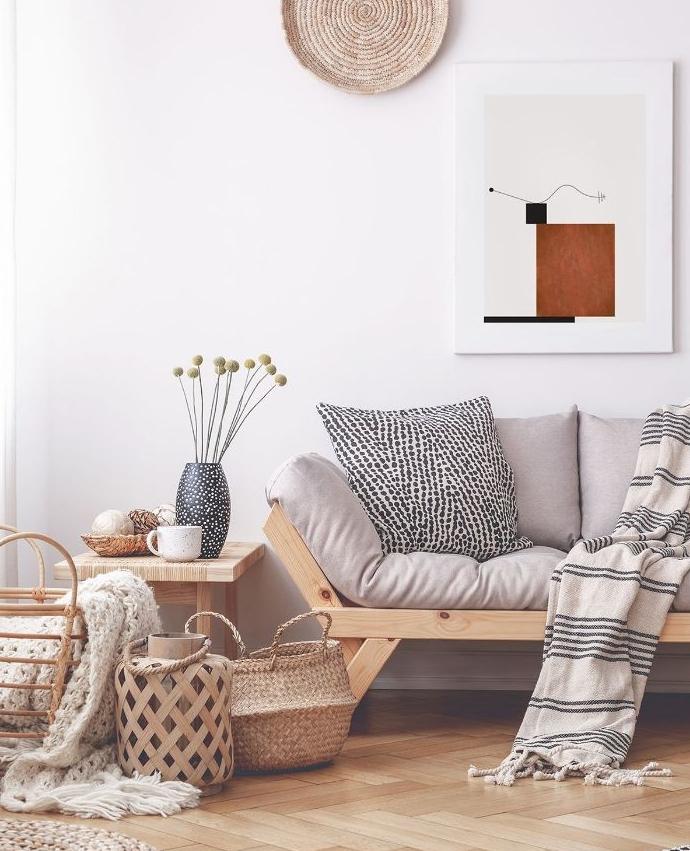 idée déco canapé bois clair décoré de coussins tapis noir et blanc paniers de rangement plaid grosses mailles cocooning