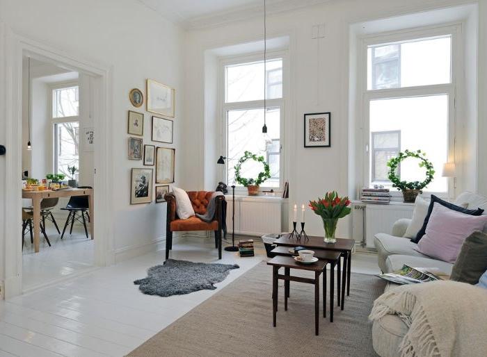 idee deco salon cosy blanc avec canapé confortable gris perle sol parquet blanchi tables bois gigognes murs blancs décorés de cadres