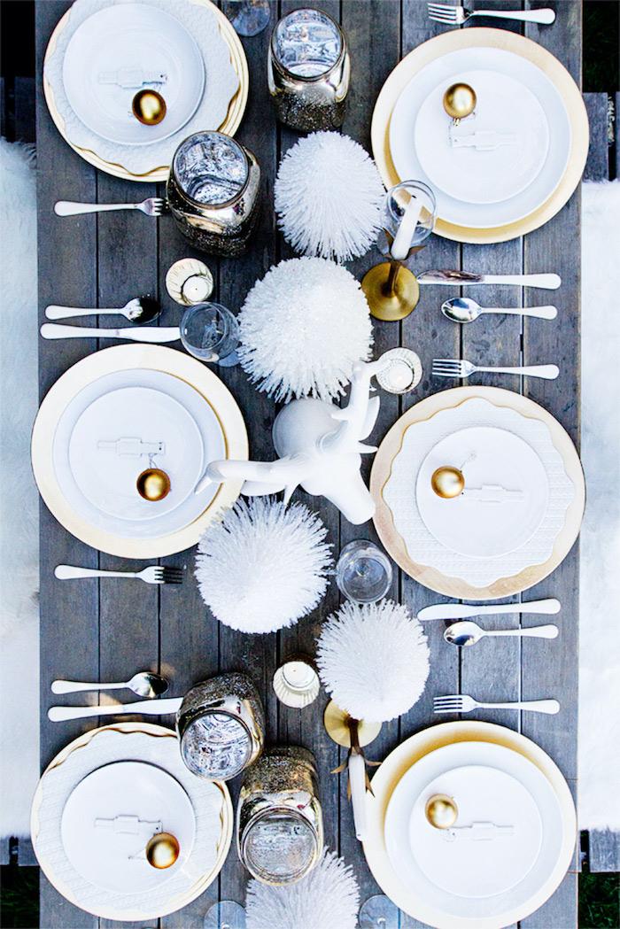 idee decoration de la table de nouvel an avec une thématique hivernale des fleurs decoratives et un cerf blanc