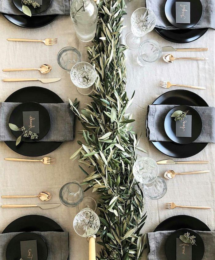 idee theme nouvel an avec un chemin de table a feuilles persistantes des couverts en or et des assiettes noirs avec des serviettes gris