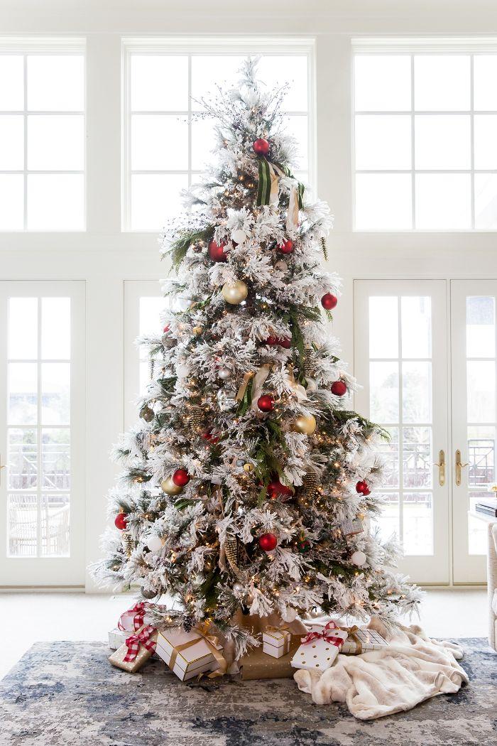 image sapin de noel à branches vertes et blanches avec des boules rouges et or et des guirlandes lumineuses noedus décoratifs peids en cadeaux