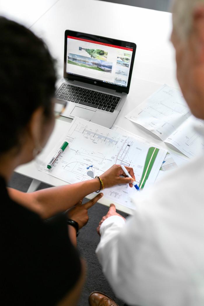 le rôle du maître d œuvre deux personnes devant un ordinatuer et des projets de construction