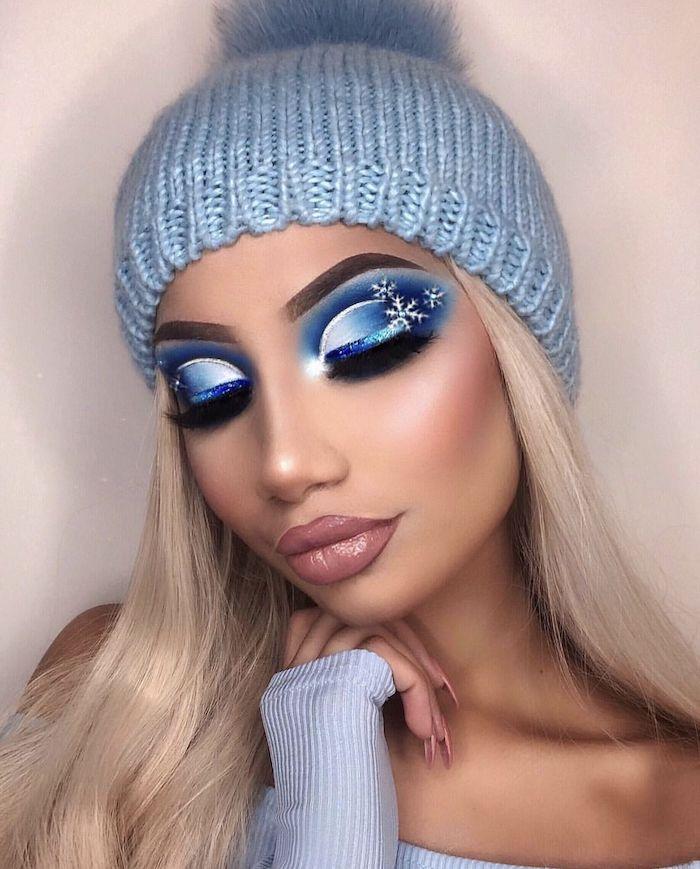 maquillage de noel avec des flocons de neige et des fards a paupieres une fille avec blouse et chapeau bleus et des des cehveux blonds