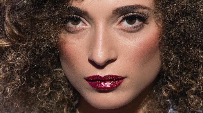 maquillage de noel avec un rouge a levre paillete une femme aux cehveux boucles
