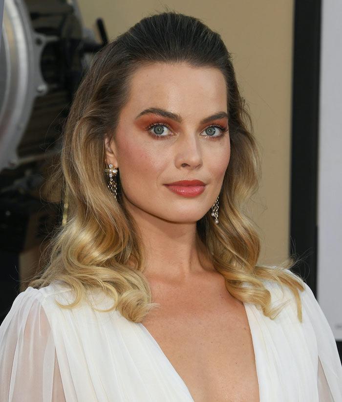 maquillage soirée avec des fades et rouge à levres en orange margot robie vetue en blouse blanche avec un col v