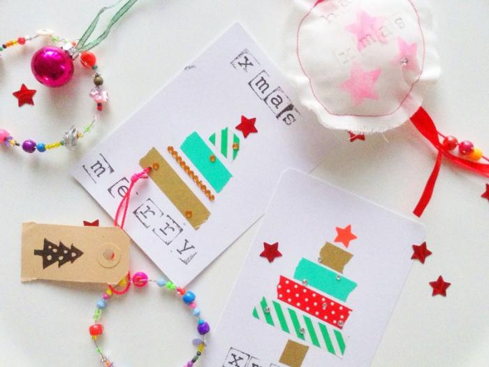 modele de sapin de noel et bandes de washi tape coloré sur papier blanc avec deco de strass et d étoiles