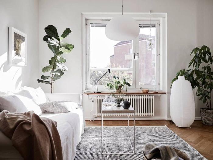 modele salon cocooning naturel avec canapé blanc plaid gris murs blancs tapis gris plantes vertes en pot