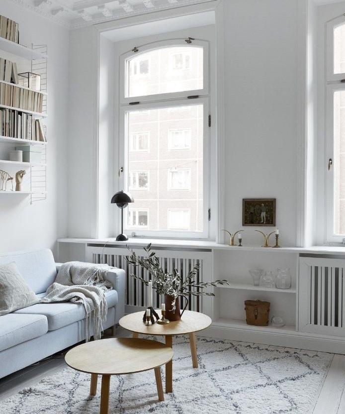 murs blancs tapis gris clair canapé blanc grandes fenetres tables gigognes ambiance cosy de salon nordique chic