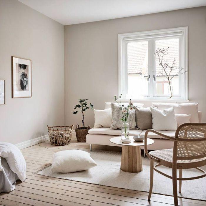 murs gris perle canapé beige décoré de coussons tapis blanc table basse minimaliste chaise cannage parquet bois clair original