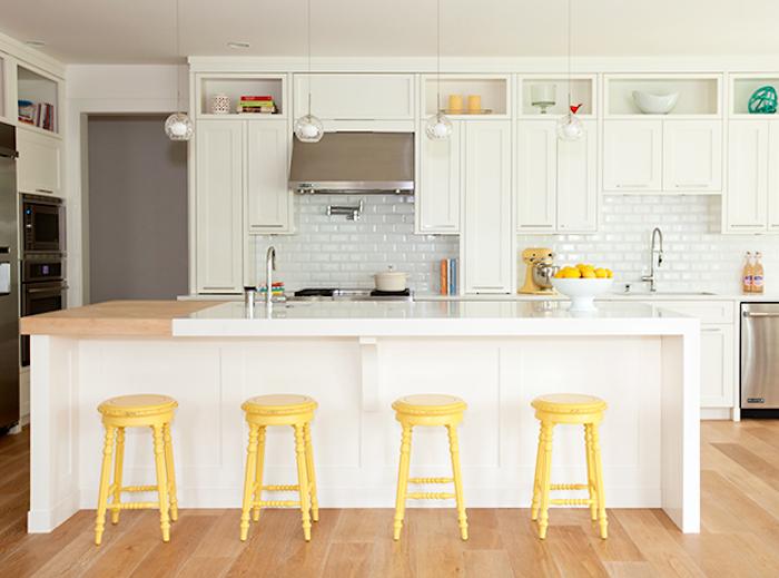 pantone 2021 tendance dans les couleurs un cuisine en blanc avec comptoir et des bar chaises en jaune lumineux