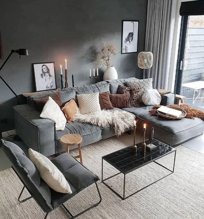 peinture mur gris foncé canapé et fauteuils gris tapis gris clair multitude de bougies table basse noire coussins colorés