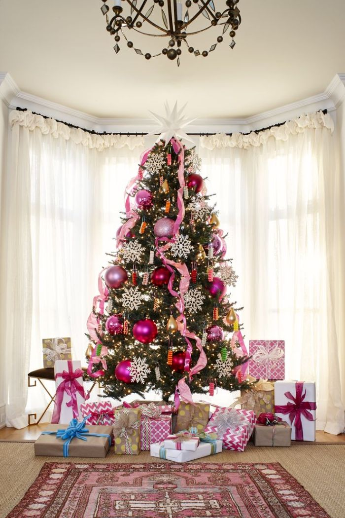 photo de sapin de noel joli décoré de boules mauves et rose gold et des flocons de neige blanches deco guirlande rubans rose pied de sapin en paquets cadeaux