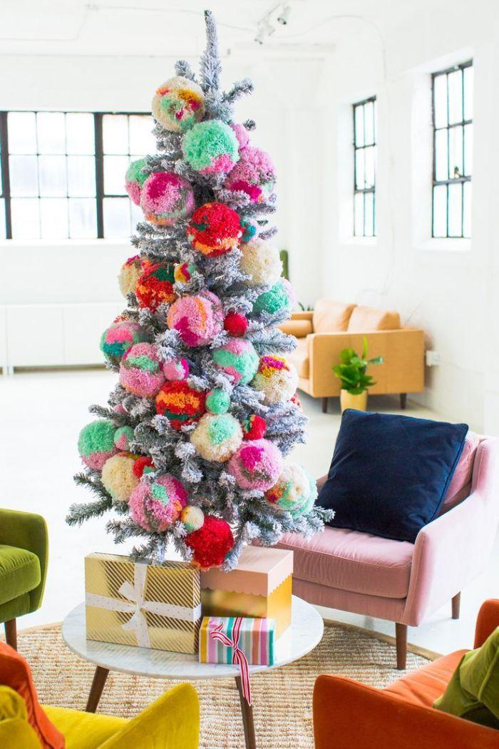 pompons colorés géants pour décorer un sapin de noel artificiel aux branches à effet enneigé dans salon moderne
