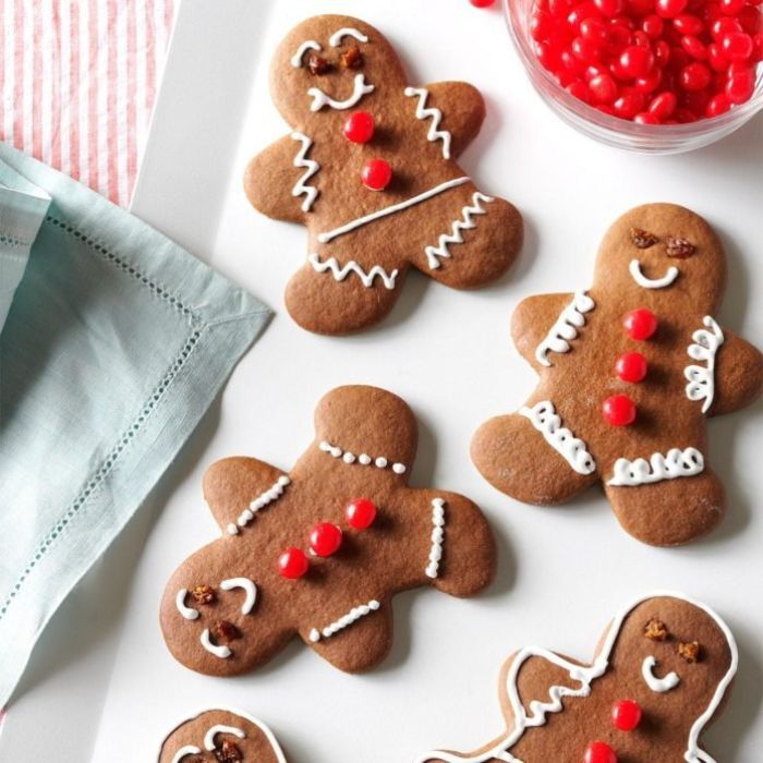 recette sablés de noel idee biscuit bonhomme en pain d épice décorée de creme fraiche et dragées rouges dans assiette blanche