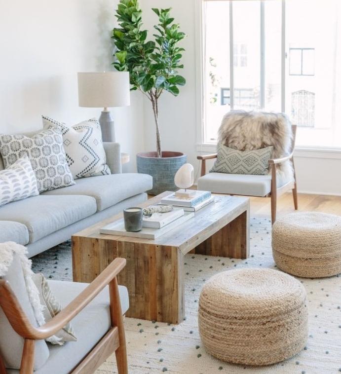 salon style scandinave avec poufs tressés canapé gris chaises et table de bois tapis cocooning berbere