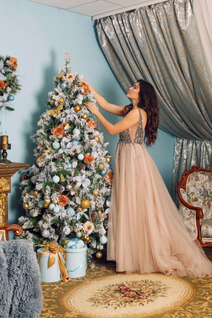 sapin de noel décoré avec des boules de noel bleu clair or et blanc et des fleurs artificielles decoratives idee deco maison noel feerique