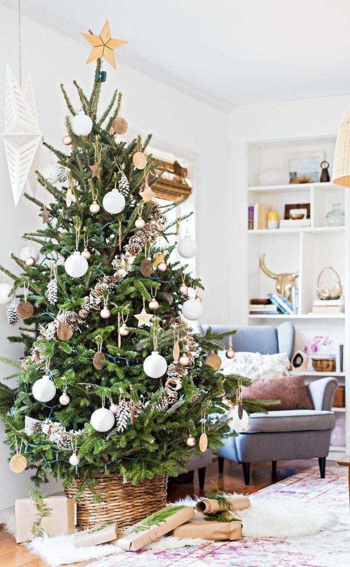 sapin de noel décoré de rondins de bois boules de noel or et blanc et des pommes de pin effet enneigé dans salon blanc