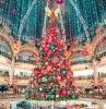 sapin de noel geant décoré de boules de noel rose et bleu et deco top d arbre en ange decoratif pluie de lumières du plafond