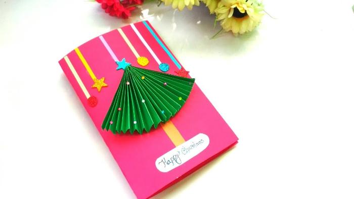 sapin de noel papier vert accordéon sur papier rose avec petites decorations et autres éléments décoratifs