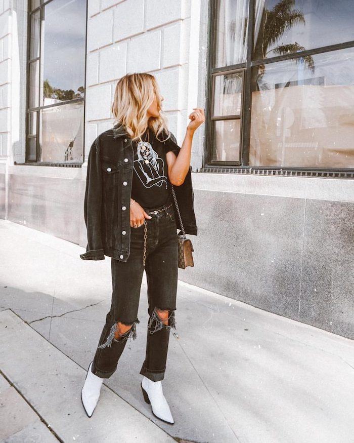 street style femme vetue en denim déchiré noir associé avec des bottes blanches