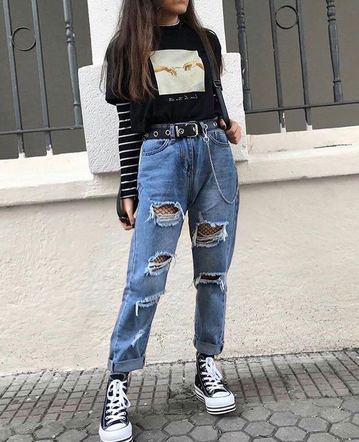 style grunge femme avec un jean dechire et des bas résillés combines avec une blouse a rayures et un t shirt dessiné