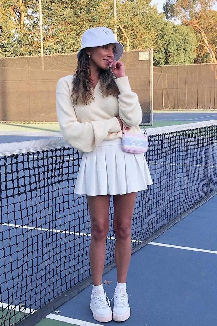 style preppy une fille vetue tout en blanc avec une fedora sur le court de tennis